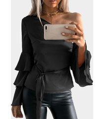 blusa negra con mangas acampanadas y volante de un hombro con cinturón