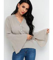 camisa gris con mangas acampanadas y cuello alto con diseño de botones
