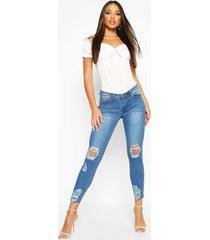 mid rise skinny jeans met versleten knie en enkels, middenblauw