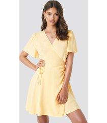 camille botten x na-kd wrap mini dress - yellow