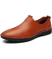 gli uomini che lavorano a mano in cuoio cucendo slip sulle scarpe casual
