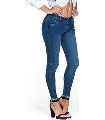 jeans skinny tono medio y ruedo rústico
