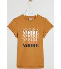 het josh v dora amore t-shirt in de kleur amber is gemaakt van een comfortabele katoenkwaliteit met stretch. het t-shirt is bedrukt met de tekst 'amore', waarvan het eerste deel geborduurd is. de pasvorm van het t-shirt is licht getailleerd. het josh v dora amore t-shirt is verkrijgbaar in de kleuren whisper white en amber.
