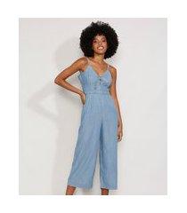 macacão jeans feminino pantacourt com nó e bolsos alça fina azul médio