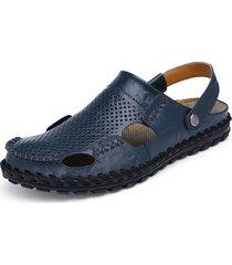 respirabile della spiaggia degli uomini che scivola fuori sui sandali di cuoio che portano due vie