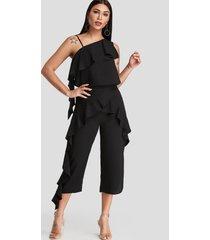 conjunto de pantalón con volantes y top de un hombro con diseño cruzado en negro
