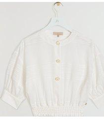 de josh v juliana blouse in de kleur whisper white is gemaakt van een luchtige katoenkwaliteit met een ingeweven streeppatroon. de pasvorm is cropped en losvallend en in de taille is de blouse voorzien van een elastieken smock tailleband. door de pofmouwen en josh v branded emaille knopen heeft de blouse een elegante look. maak je look compleet en combineer de top met de bijpassende verona rok in de kleur whisper white. de josh v juliana blouse is verkrijgbaar in de kleuren summer skin & whisper white.
